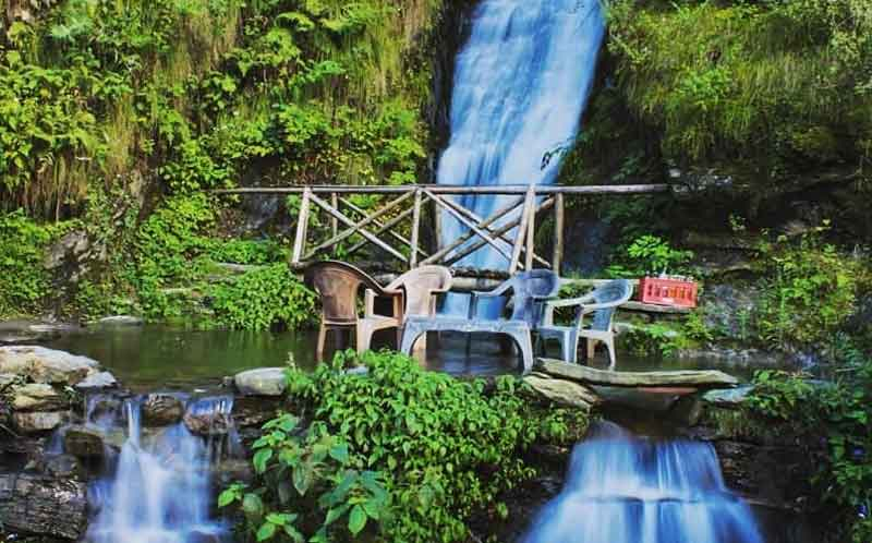 water falling from the top of mountain range and passing through the area surrounds with chairs and wooden bridge at Jana Waterfall