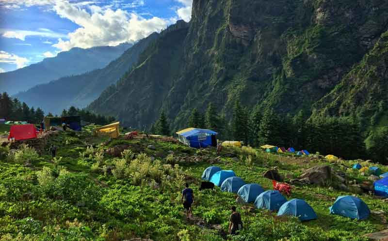 On the mountain lush greenery range, people camping around after trekking to the top of kheerganga peak to see the beautiful landscape.