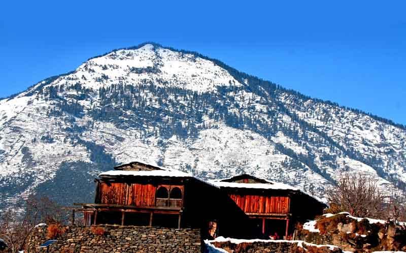 snow-clapped mountains featuring slop mounted houses and snow everywhere in Naggar village