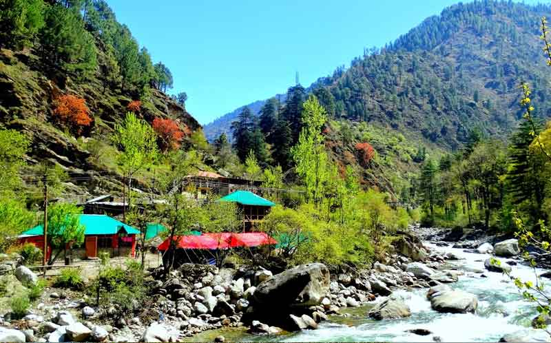 Houses around the river flowing and mountain ranges along with trees in Tirthan valley