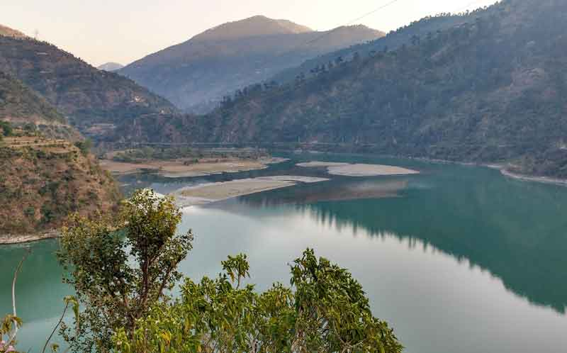The pandoh dam and lake surrounds the mountains hills long tree and lush greenery environment.